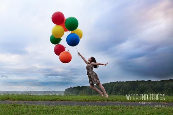 Senior portrait of girl being carried away by a bunch of balloons. My Friend Teresa Studios