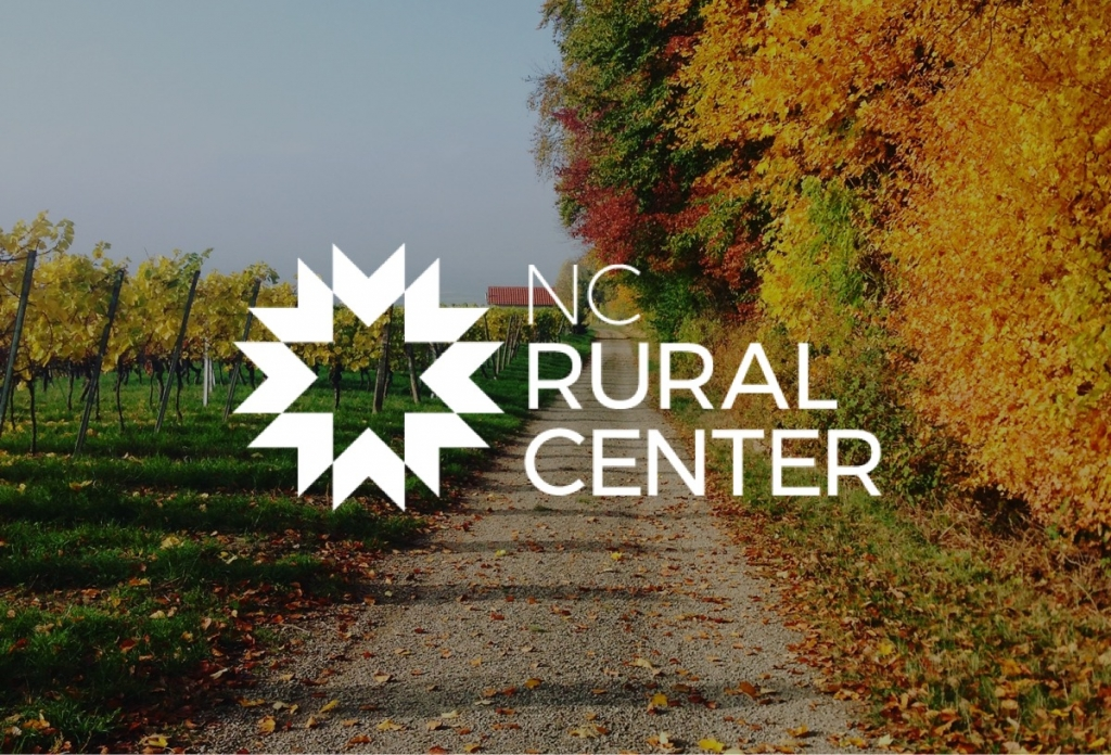 The new NC Rural Center logo in white on top of a photograph of a country road in autumn.