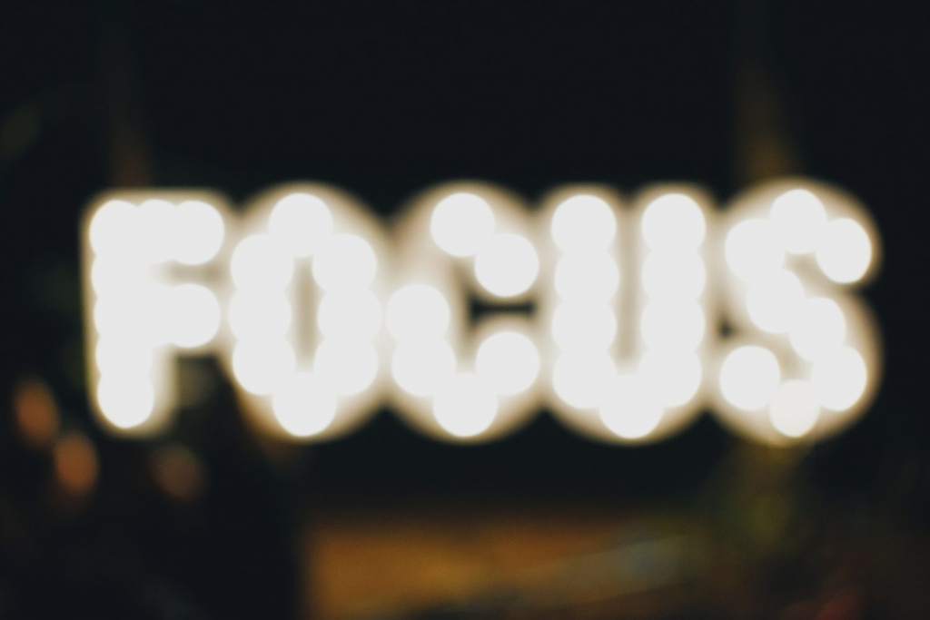 Blurry photograph of the word FOCUS spelled in lights