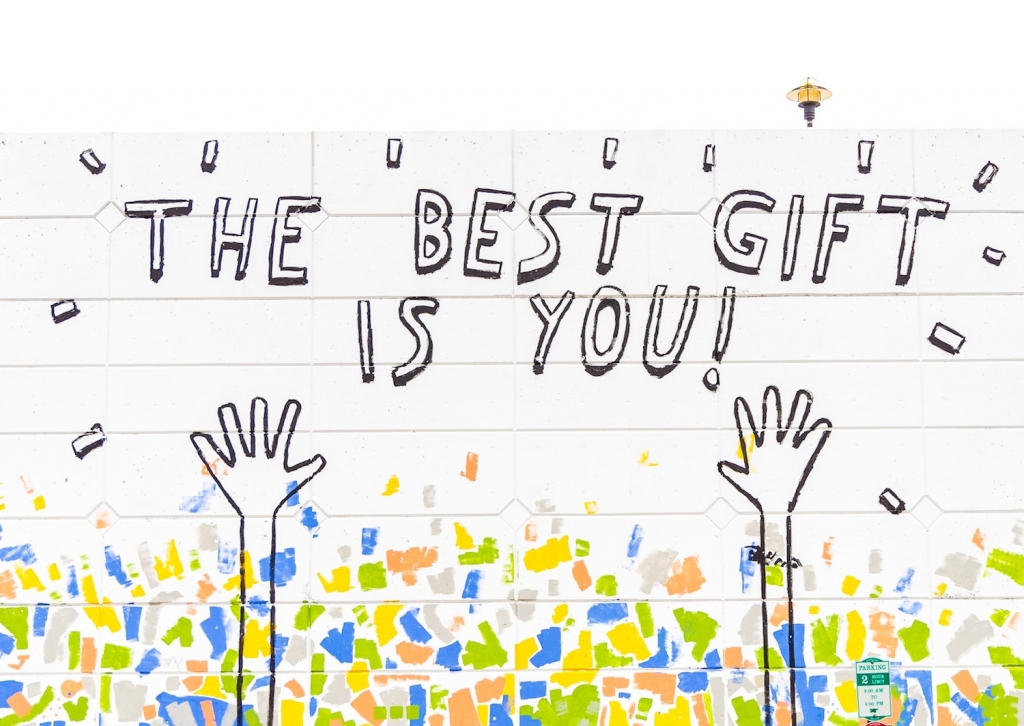 Large mural on white wall that says The Best Gift Is You!