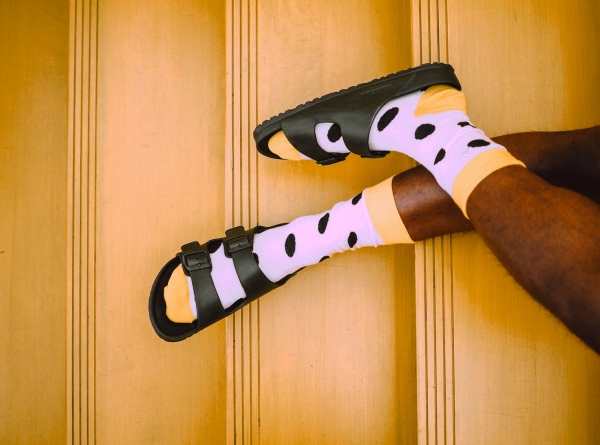 Man wearing polka-dot socks with sandals on yellow stairs