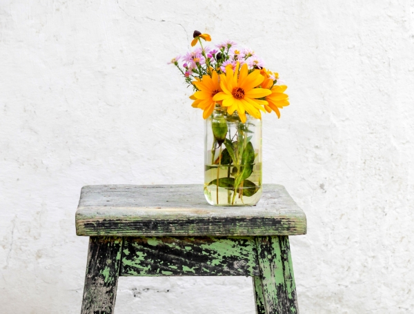 A simple vase with yellow and purple wildflowers, resting on a wooden stool.