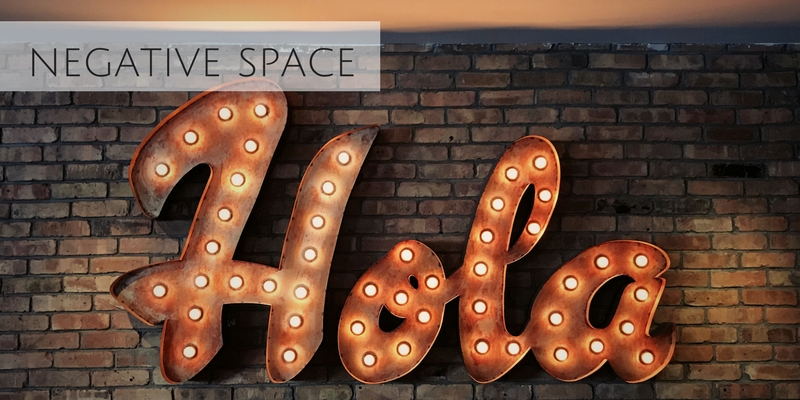 Beautiful stock photograph of a lighted sign that says Hola from Negative Space