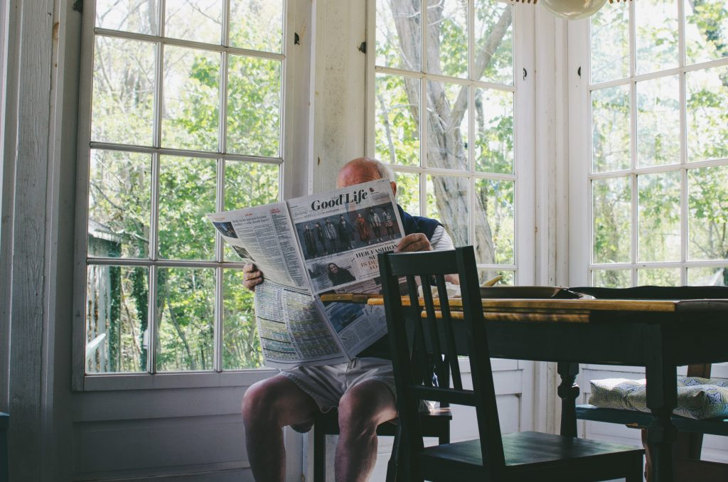 Elderly man reading a newspaper in shorts at a sunny kitchen table