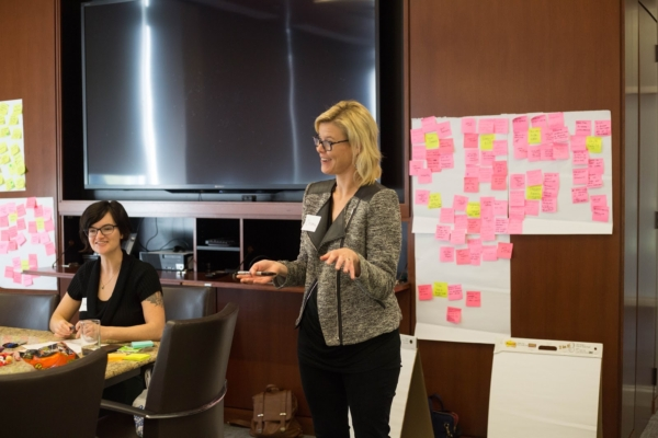 Christina is standing at the front of a conference room speaking with large sheets of paper with pink sticky notes behind her. Alisa is sitting at the head of the conference table watching Christina.