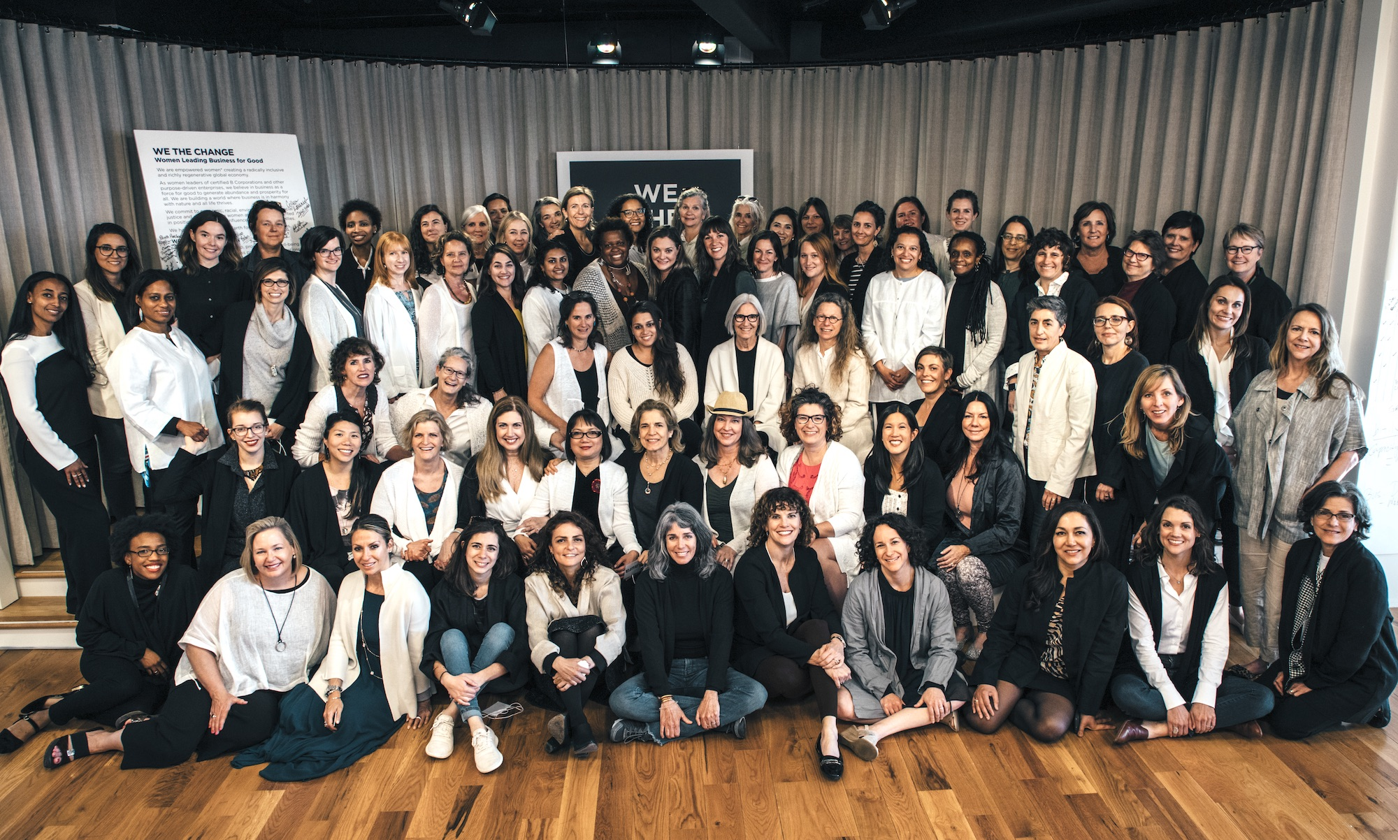100 women CEOs of B Corporations gathered on a stage, wearing black and white tops.