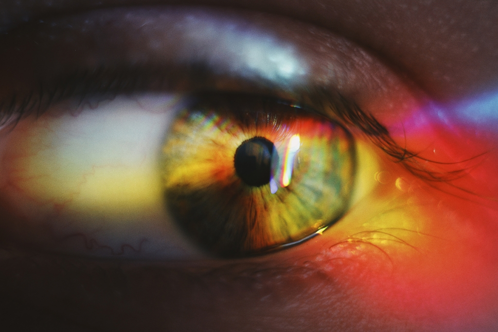 Close up of a person's eye reflecting rainbow colors