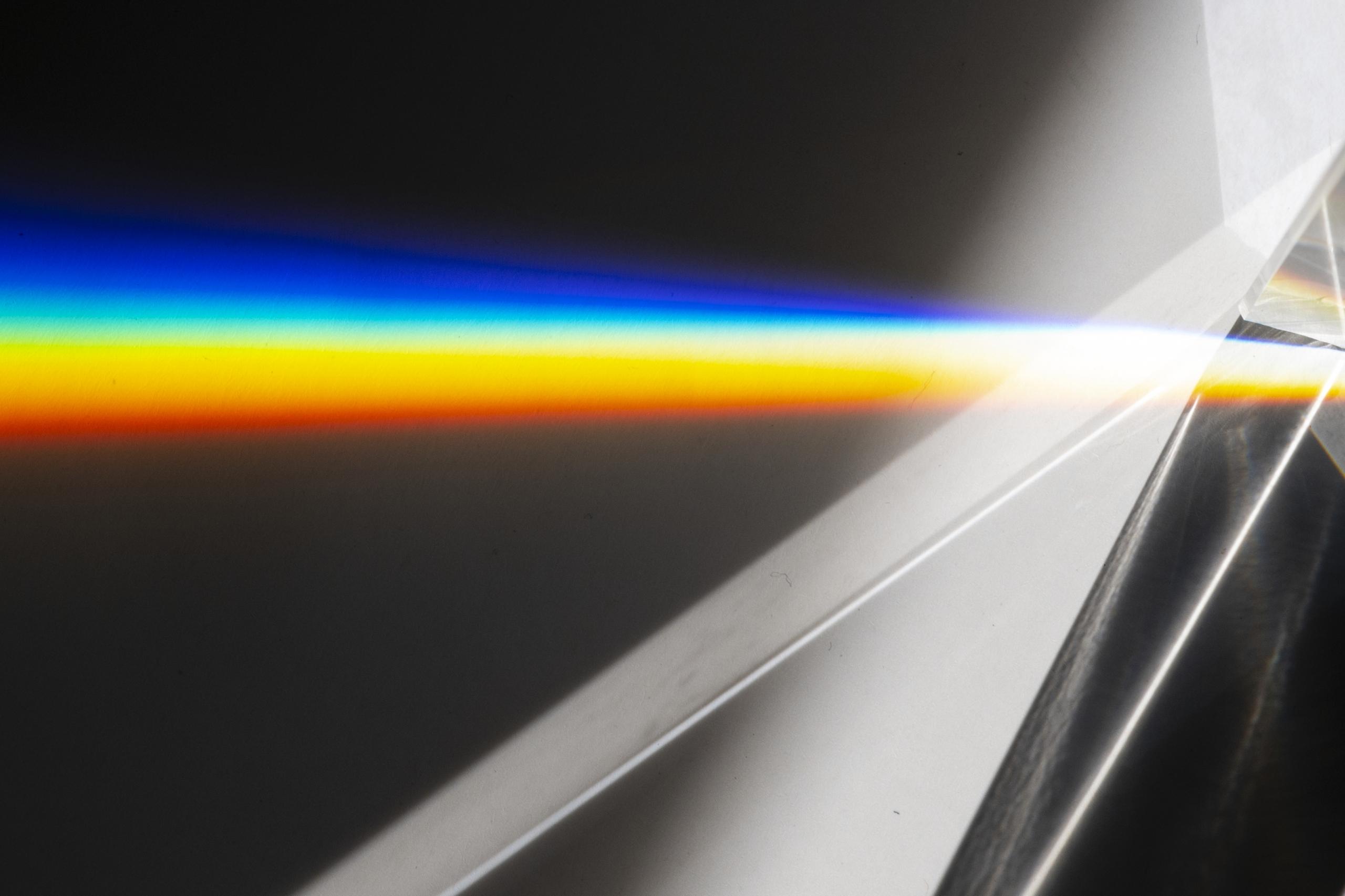 Light beam shining through a prism creating a rainbow beam.