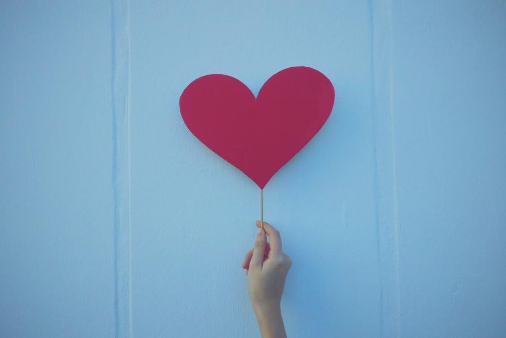 A person holding up a papier-mâché heart