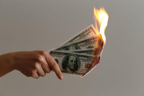 A person holding burning hundred dollar bills