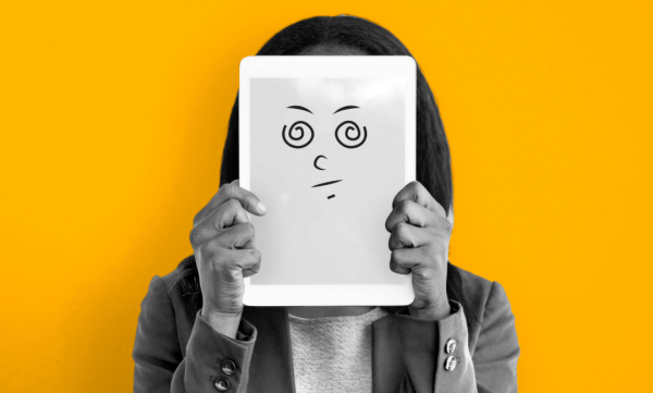 A woman holding up a whiteboard with a confused face on it.