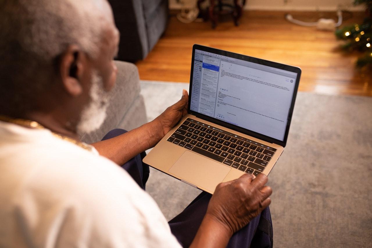 An old black man using an Apple laptop