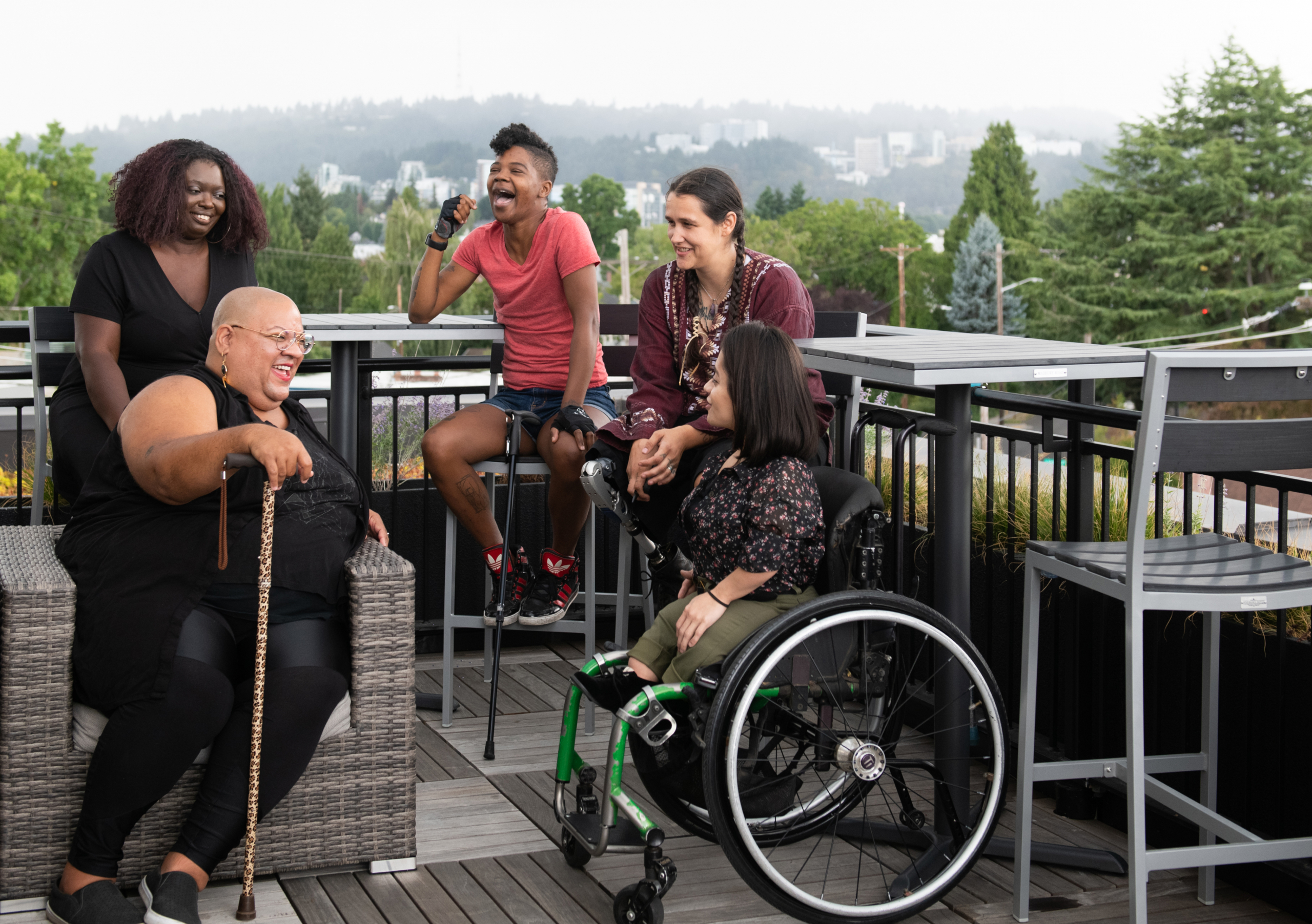 A group of disabled black women and latinas laughing on a patio